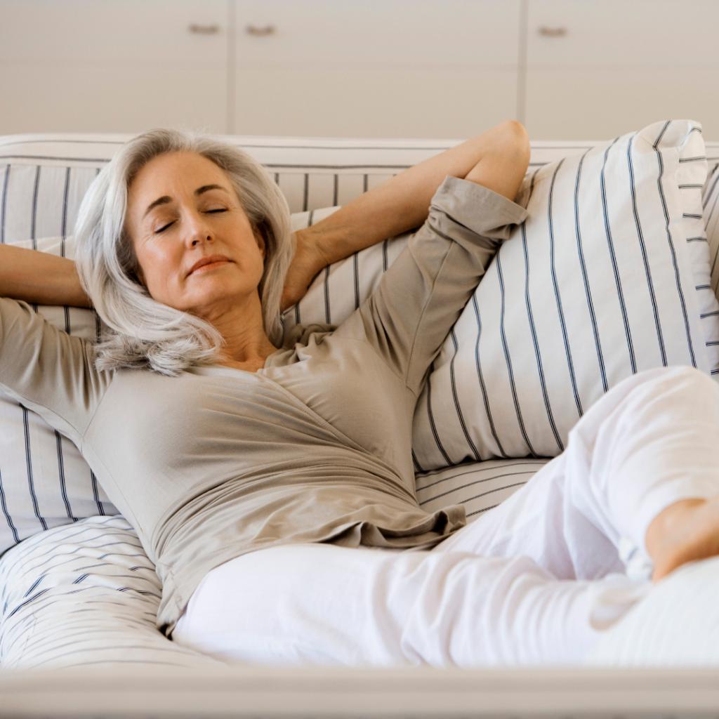 Kvinna sitter avslappnad i soffa