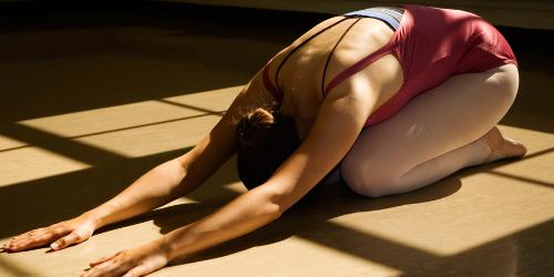 Kvinna ligger framåtböjd på en yogamatta i barnets position